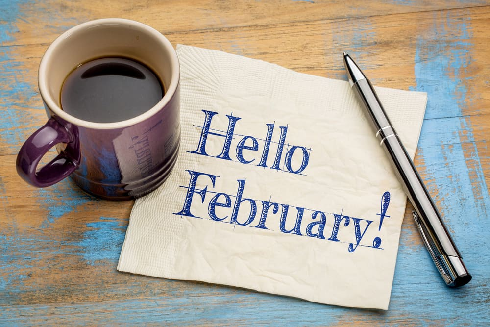A cup of coffee on a table, with February and Text