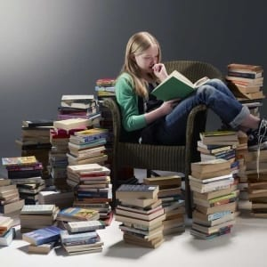 A woman sitting next to a book shelf