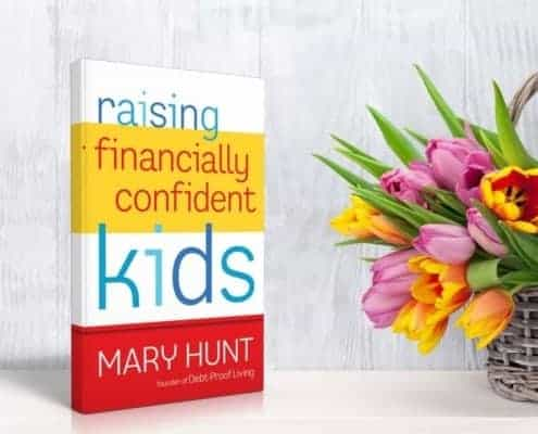 Raising Financially Confident Kids Book sitting on a white shelf with basket of bright colored tulips