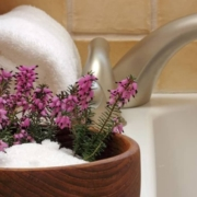 Flower in bowl next to bath tub