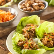 A bunch of food on a plate on a table, with Lettuce and Wrap