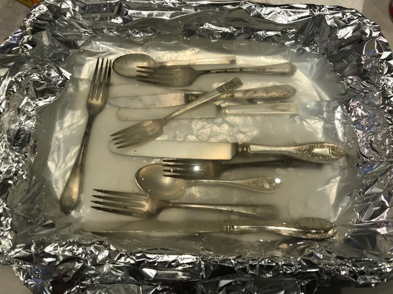 Tarnished silver flatware in homemade silver cleaning solution