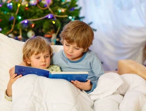 Two little blond sibling boys reading a book together in bed near Christmas tree.