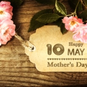 "wooden sign surrounded by pink flowers with the words ""Happy May 10, 2020 - Mother's Day"" on it"