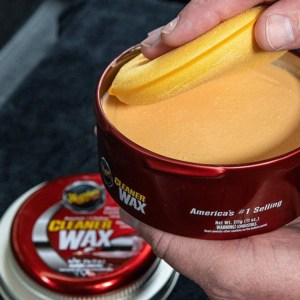 Male hands holding can of car wax and sponge applicator