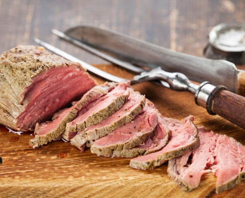 A piece of meat on a wooden cutting board