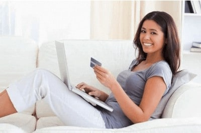 Young women shopping online with a credit card in her hand and a smile on her face