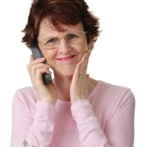 mature woman in pink sweater with a worried look on phone