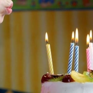 A plate of food with a birthday cake, with Candle