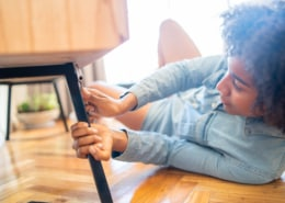 Afro woman repairing furniture at home.