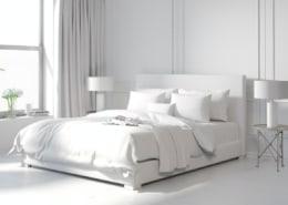 white bedding on white bed in white room