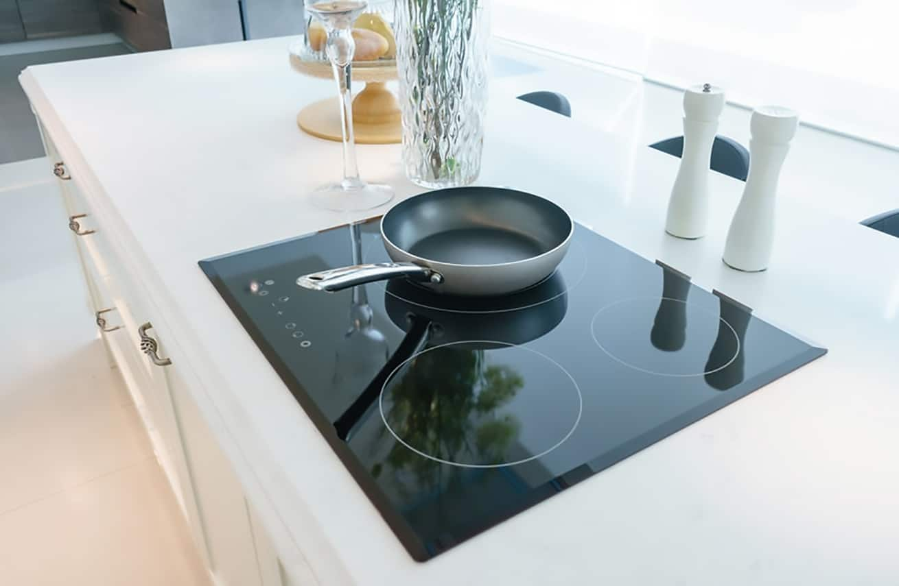 Frying pan on modern black glass electric stove, built in cooktop with ceramic top in white kitchen interior