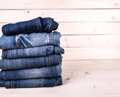 Six pairs fashionably faded blue denim jeans neatly stacked