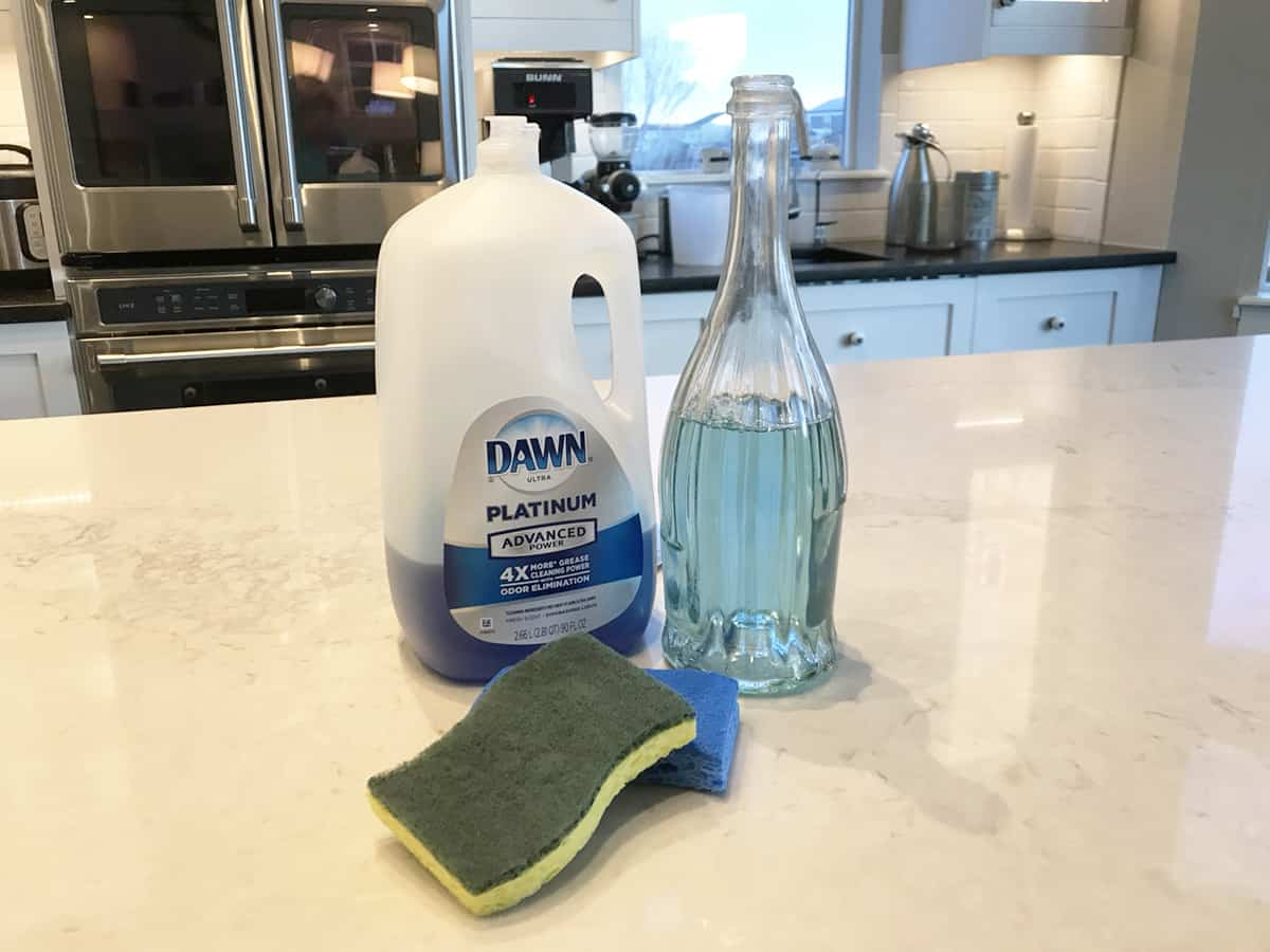 bottle of blue dawn on counter with a glass decanter showing how to dilute it to stretch farther