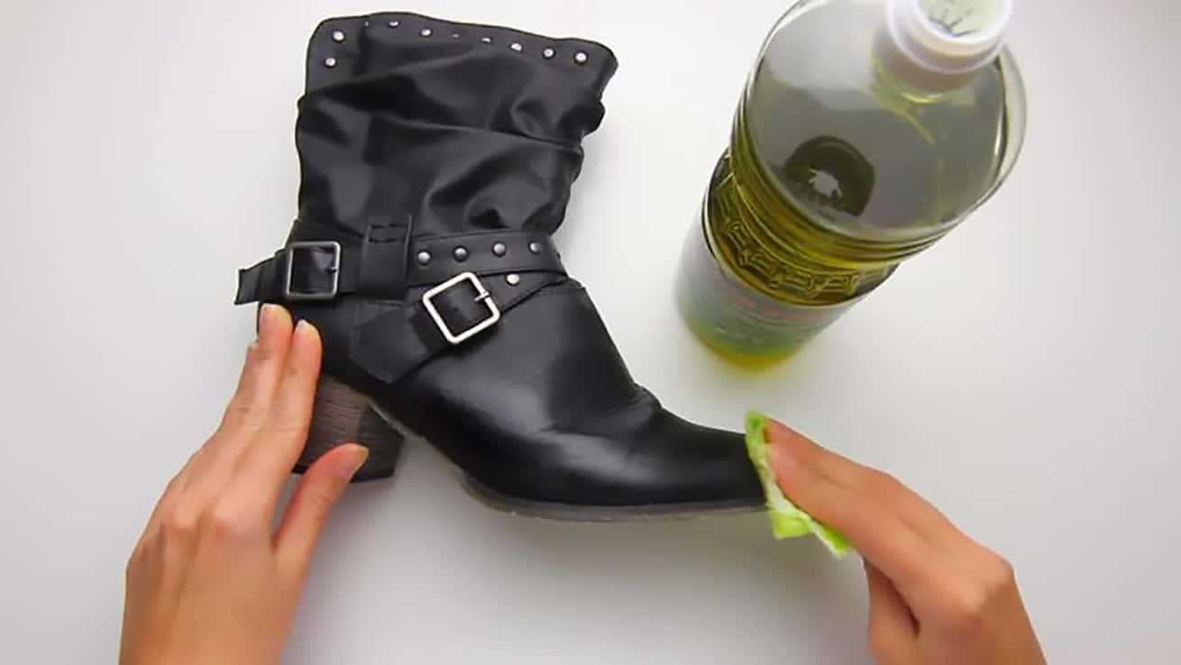 female hands cleaning black leather boot with olive oil