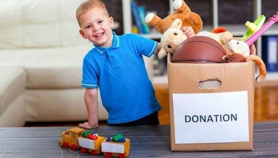 Boy taking donation box full with stuff to donate