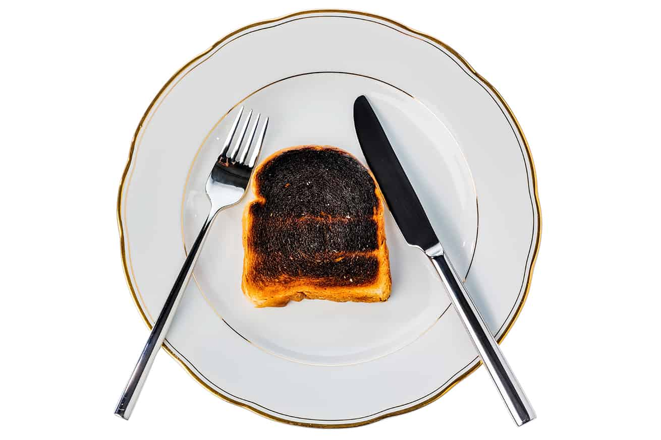 burnt grilled cheese sandwich on white plate with fork and knife