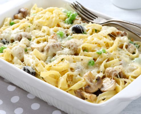 A bowl of pasta sits on a plate, with Casserole
