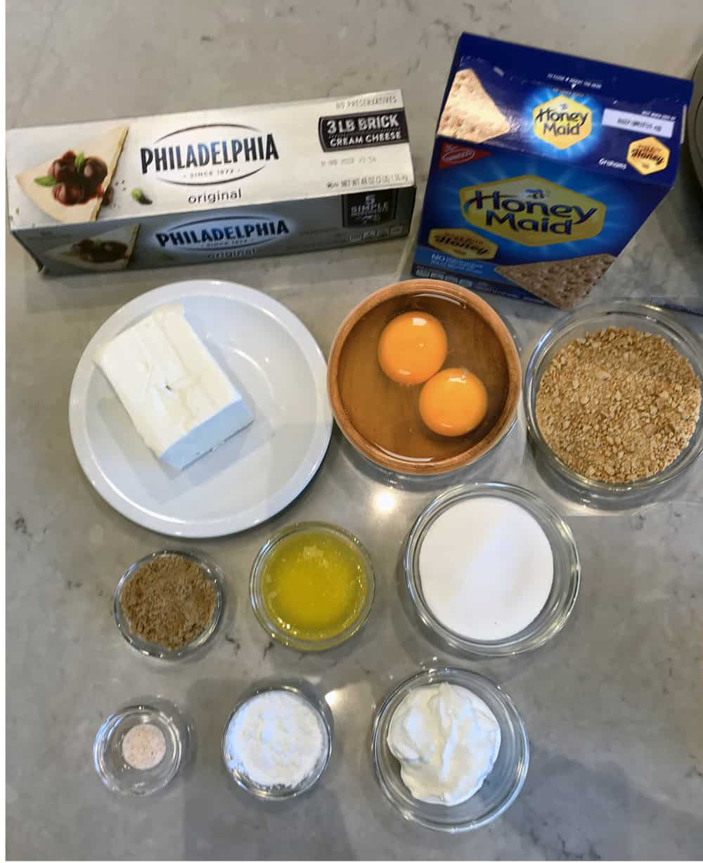 individual ingredients in bowls all ready to make homemade New York Cheesecake