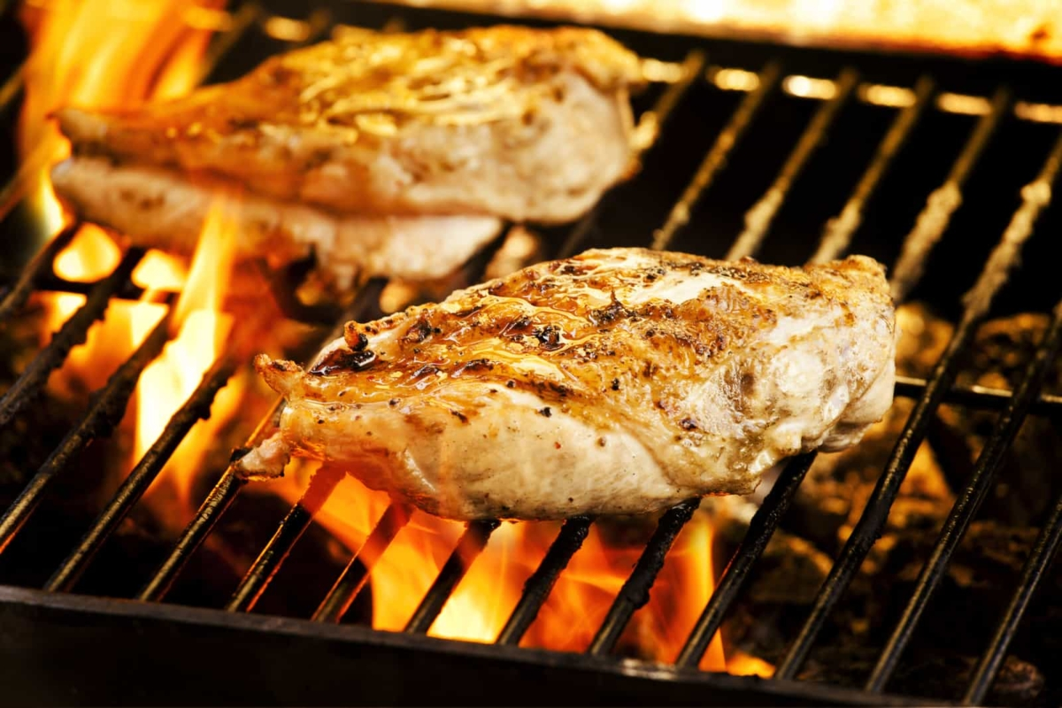 two chicken breasts on the outdoor grill perfectly cooked and ready to eat