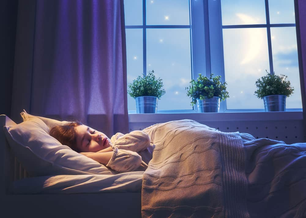 A person sitting on a bed next to a window