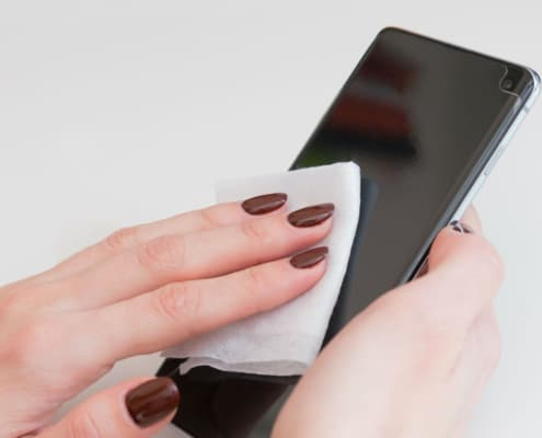 Womans hand cleaning smartphone screen with alcohol. Concept of Cleaning dirty screen phone for disease prevention from virus Covid-19.