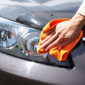 Hand with microfiber cloth cleaning car headlight covers.