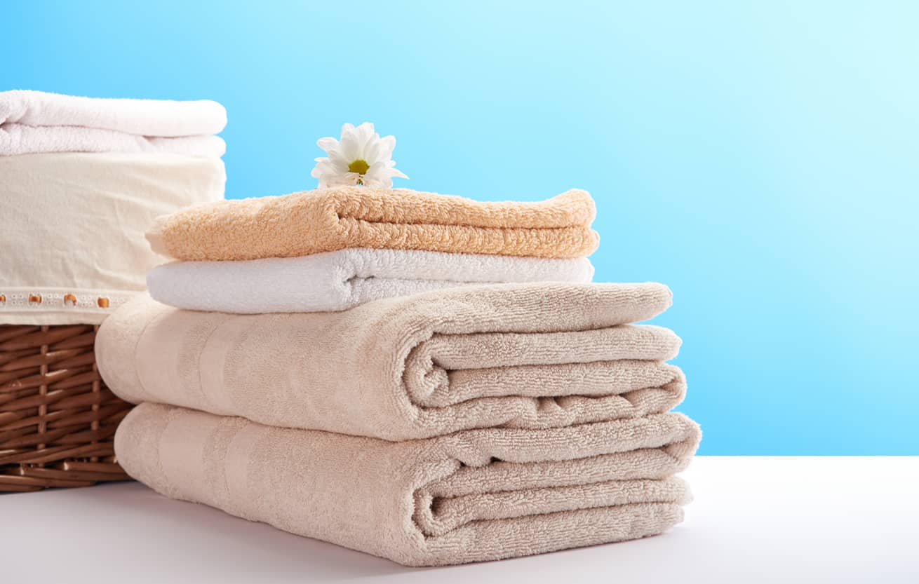 pile of clean soft towels, chamomile flower and laundry basket on blue