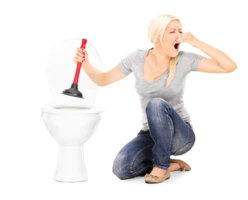 Woman unclogs a stinky toilet with plunger