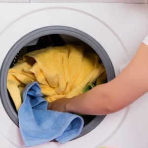 woman removing clothes and towels from clothes dryer