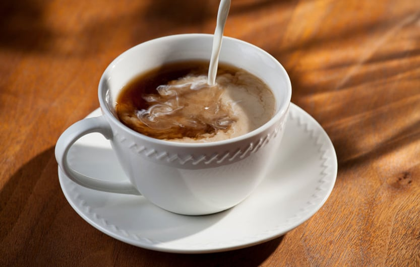 Cup of Coffee and Pouring Creamer