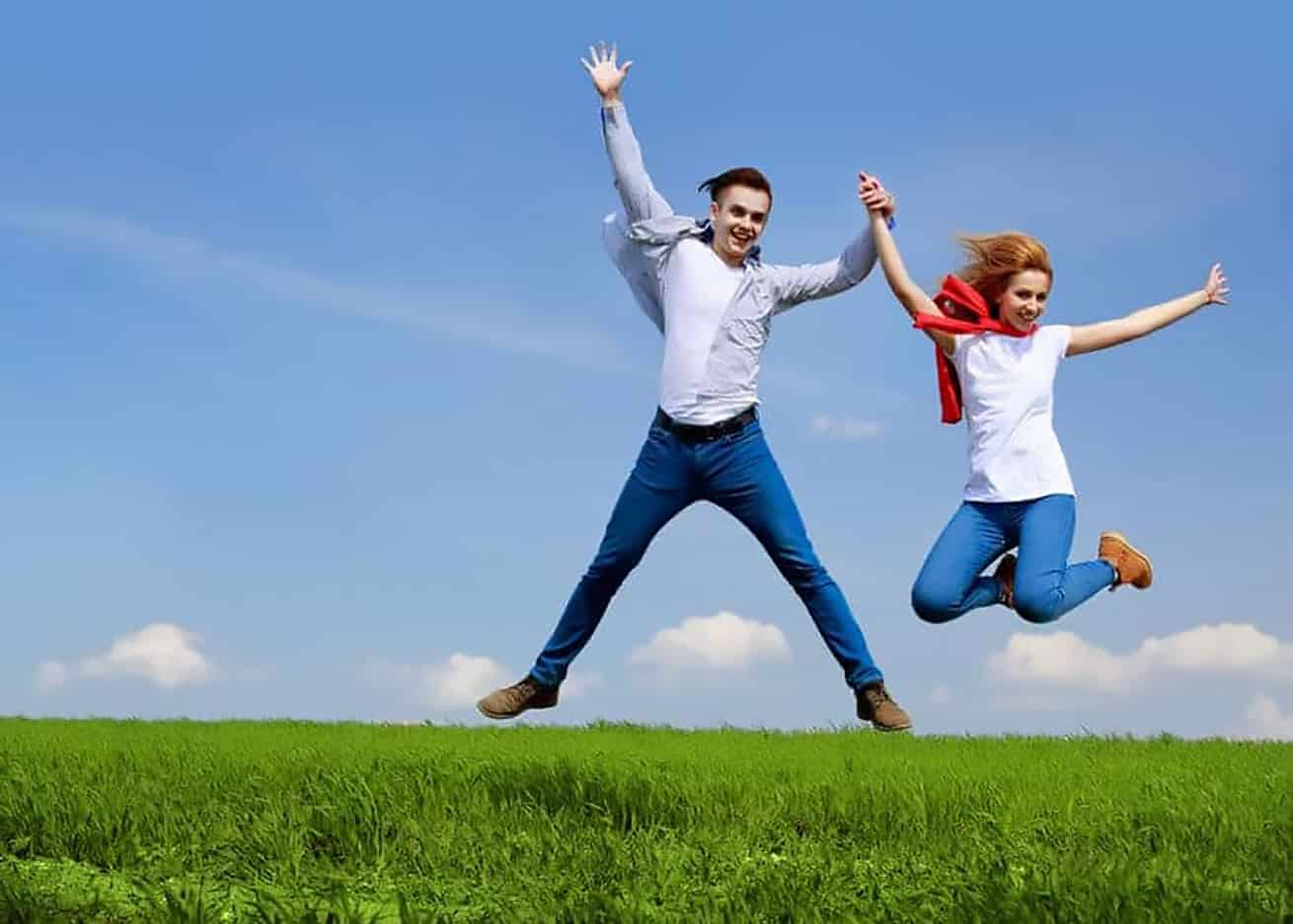 couple jumping in field of green with blue sky background
