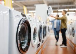 Couple choosing washing machine, electronics store