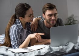 couple planning a year without spending using laptop