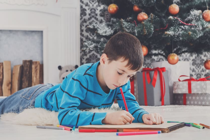 Cute boy writing letter to santa, waiting for christmas