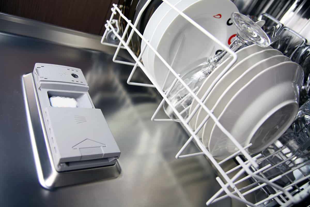 open dishwasher with clean plates in it, focus on dishwasher detergent