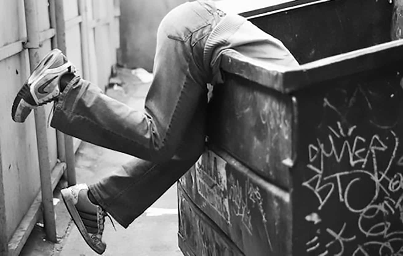 man diving into dumpster