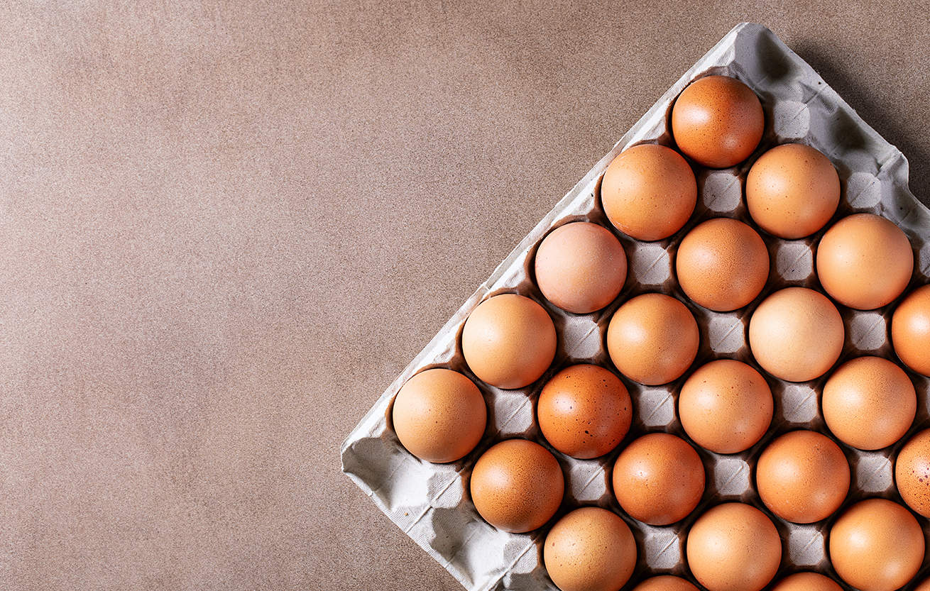 Eggs in carton box over brown texture background. Top view, flat lay