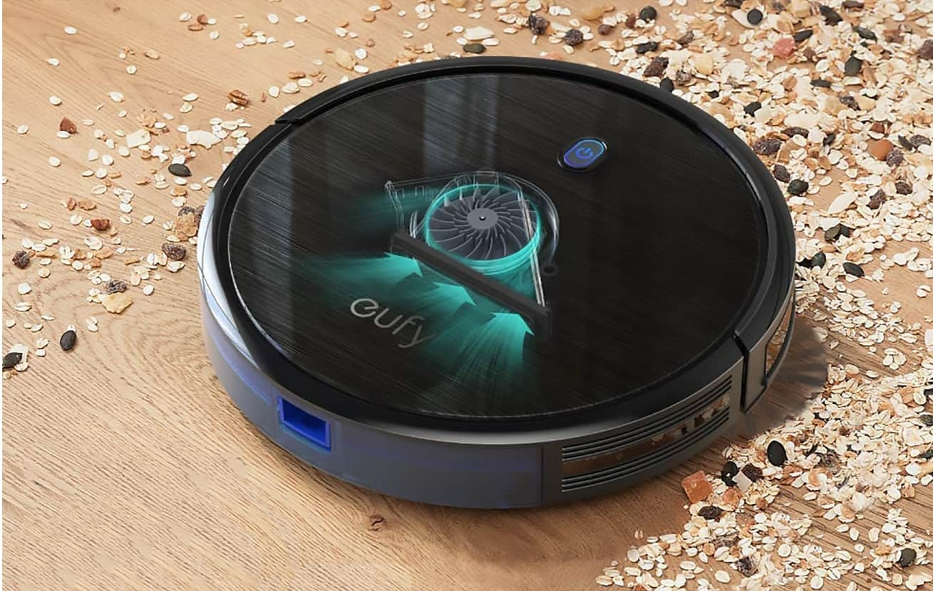 eufy robovac 11S black vac on wood floor showing how it picks up debris