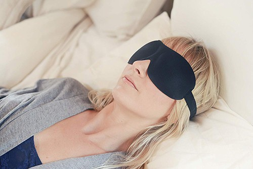 Young college student alseep wearing a black eye mask