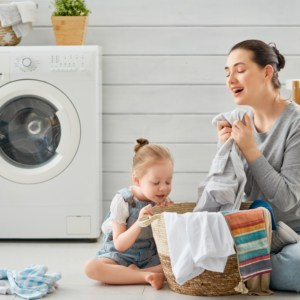 woman and child using fabric softener in laundry room