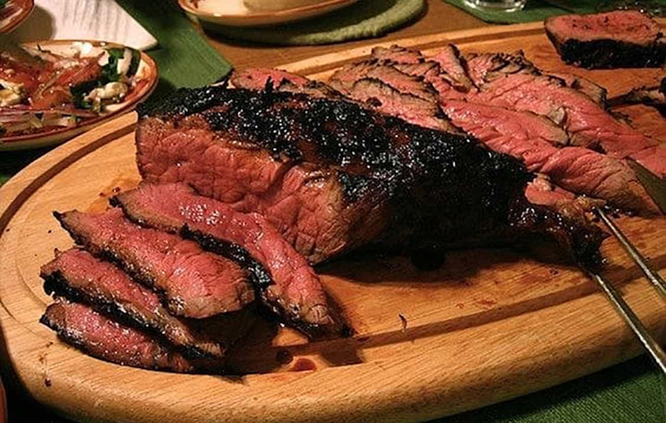 flank steak sliced on wood platter