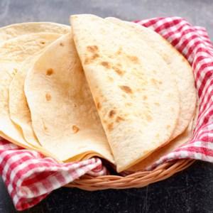 homemade flour tortillas in a wicker basket