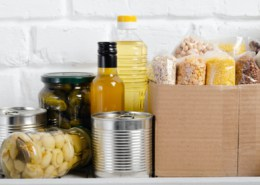 Set of uncooked foods on pantry shelf prepared for disaster emergency conditions on brick wall background closeup view
