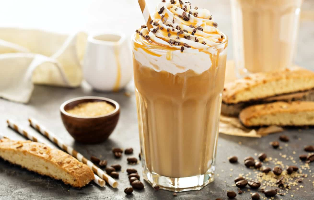 Iced frappochino coffee in a tall glass with syrup and whipped cream