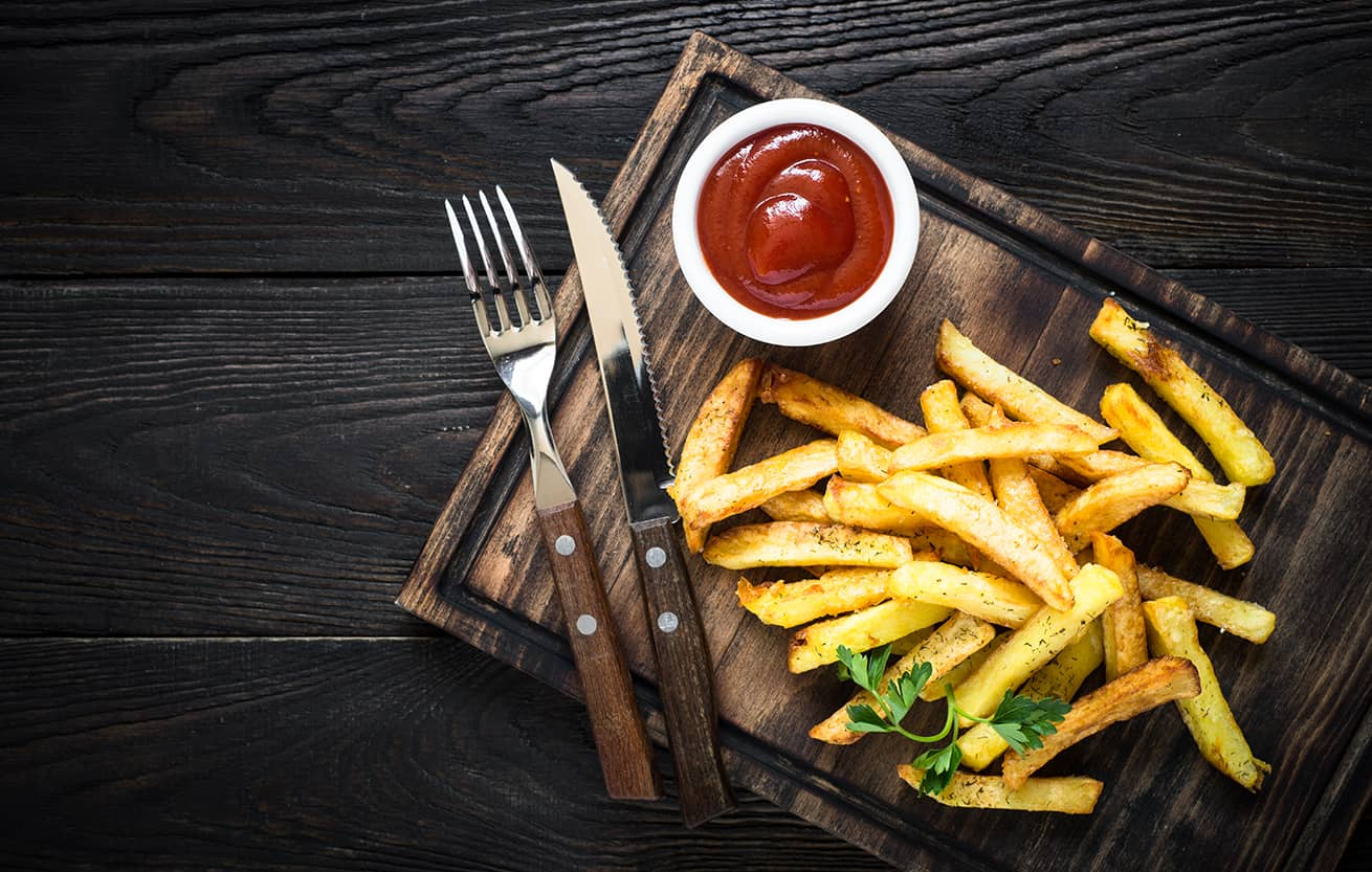 French fries with ketchup on wood tray