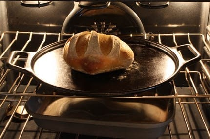 A close up of a metal pan on a stove top oven, with Bread and Dough