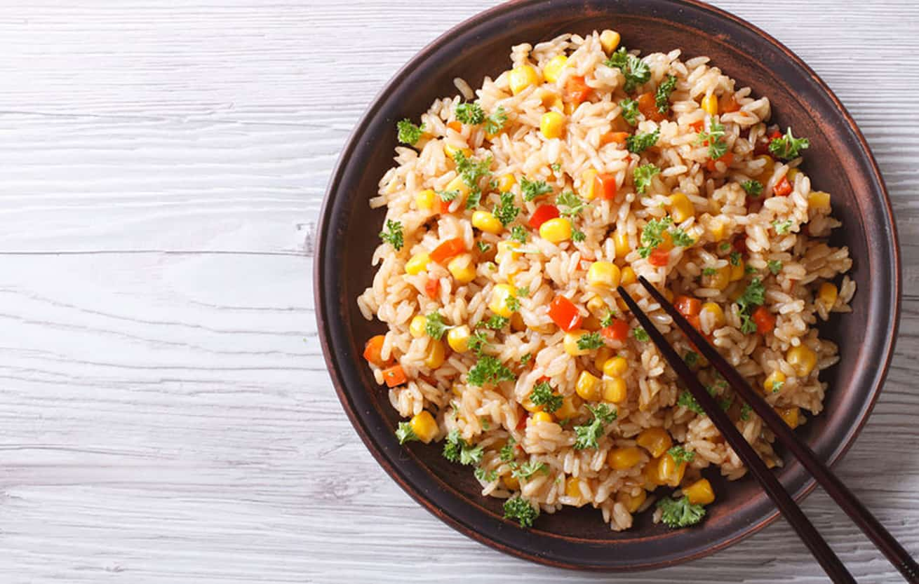 fried rice in a brown bowl with chopsticks