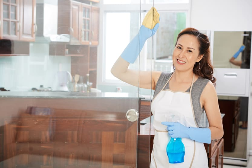 Pretty smiling housewife doing general cleaning in kitchen