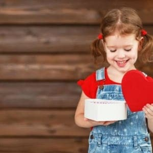 Little Girl Opening Valentine's Day Gift